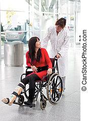mujer, con, pierna en yeso, sílla de ruedas, y, enfermera