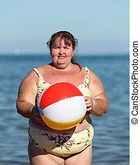 mujer con sobrepeso, con, pelota, en, playa