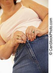 mujer con sobrepeso, tratar, abrochar, pantalones