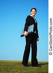 mujer de negocios, aire libre, tenencia, computador portatil
