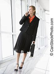 mujer de negocios, ambulante, en, pasillo, el hablar en el teléfono portátil