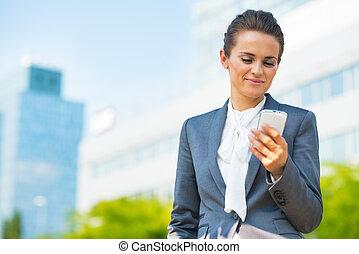 mujer de negocios, con, teléfono celular, en, oficina, distrito