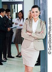 mujer de negocios que está de pie, en, oficina, con, colegas, fondo