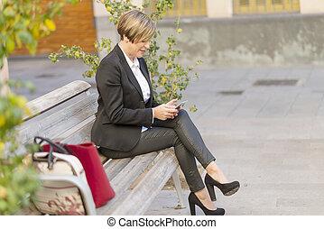 mujer de negocios, utilizar, smartphone, mientras, sentado, en, parque de la ciudad, banco