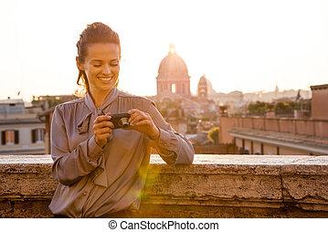 mujer, elegante, verificar, roma, fotos, cámara, sonriente