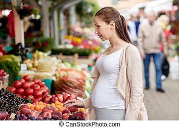 mujer, embarazada, alimento, calle, escoger, mercado