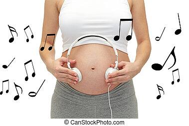 mujer, embarazada, auriculares, arriba, barriguita, cierre