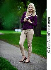 mujer, en el estacionamiento, con, teléfono celular