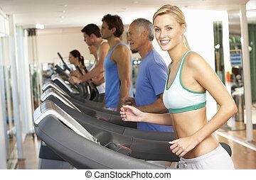 mujer, en, máquina corriente, en, gimnasio