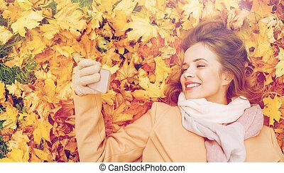 mujer, en, otoño sale, toma, selfie, por, smartphone