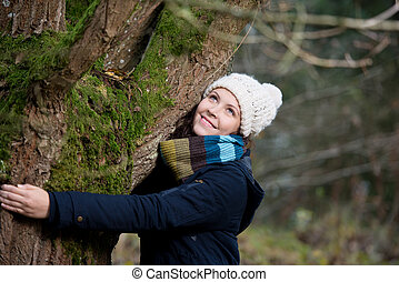 mujer, en, ropa de invierno, se abrazar, árbol