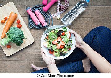 mujer, en, sportwear, tenencia, un, plato, de, fresco, ensalada, con, fresas, y, kiwi, forma de vida sana
