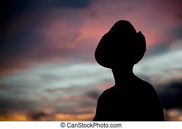 mujer, en, un, sombrero vaquero, silhouetted, contra, un, ocaso, sky.