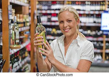 mujer, estante, supermercado, vino
