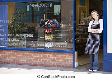 mujer estar de pie, en entrada, de, restaurante, sonriente