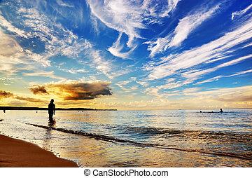 mujer estar de pie, en, ocean., dramático, cielo de puesta de sol