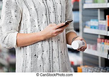 mujer, exploración, botella, con, elegante, teléfono