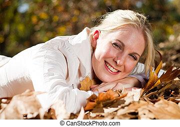 mujer feliz, acostado, en, otoño sale
