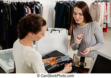 mujer feliz, cliente, pagar, con, tarjeta de crédito, en, moda, sala de exposición