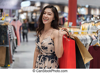 mujer feliz, con, bolsas de compras, en, tienda ropa