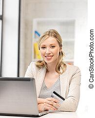mujer feliz, con, computadora de computadora portátil, y, tarjeta de crédito