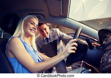 mujer feliz, con, consecionario de automóviles, en, automóvil, exposición, o, salón