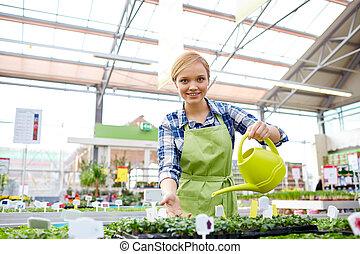 mujer feliz, con, regadera, en, invernadero