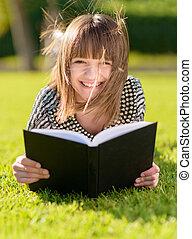 mujer feliz, libro de lectura, en el estacionamiento