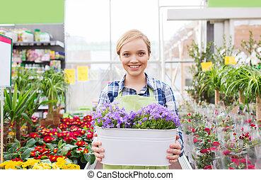 mujer feliz, sostener las flores, en, invernadero