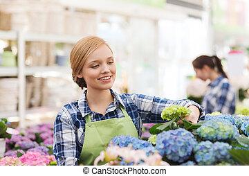 mujer feliz, tomar cuidado de, flores, en, invernadero