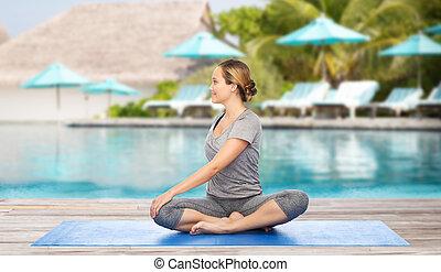 mujer, felpudo de yoga, postura, torsión, elaboración