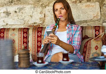 mujer, fumar, un, narguile, y, usos, smartphone, en, un, café, en, estambul, pavo
