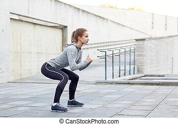 mujer, hacer, cuclillas, y, ejercitar, aire libre