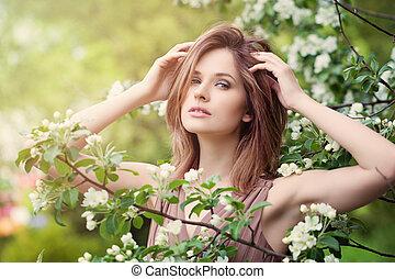 mujer hermosa, con, flores del resorte, en, luz del sol