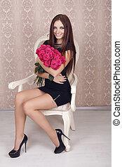 mujer hermosa, con, un, grande, ramode flores, en, ella, brazos, se sentar sobre el sillón de la presidencia, moderno, interior.