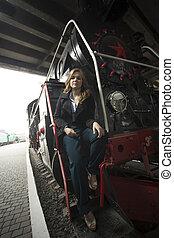 mujer hermosa, en, abrigo negro, posar, en, escaleras, de, retro, vapor, locomotora