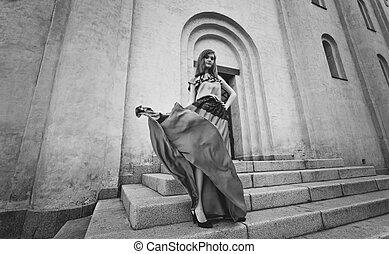 mujer hermosa, en, largo, vestido, posar, en, escaleras, en, día ventoso