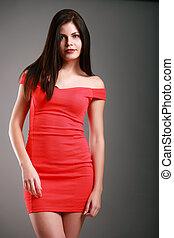 mujer hermosa, en, un, vestido rojo, en, un, fondo gris