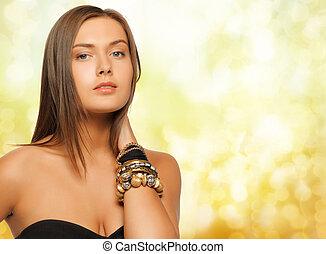mujer hermosa, encima, luces amarillas, pulseras