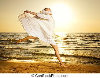 mujer hermosa, joven, saltar, playa puesta sol