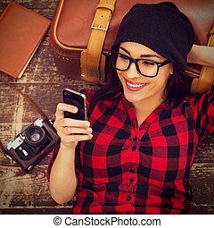 mujer hermosa, piso, móvil, cima, headwear, joven, teléfono, tiempo, tenencia, break., sonriente, toma, acostado, vista