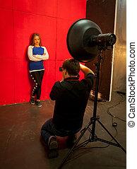 mujer hermosa, posar, en, photostudio, encima, fondo rojo