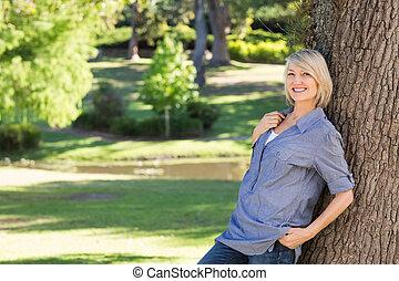 mujer hermosa, reclinado, tronco de árbol