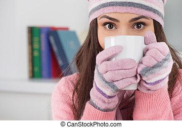 mujer hermosa, sentado, té, joven, mientras, flue., guantes, hogar, frío, sombrero, bebida