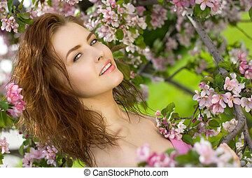 mujer hermosa, sonrisa, en flor, huerto