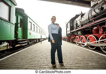 mujer hermosa, uniforme, plataforma, posar, ferrocarril