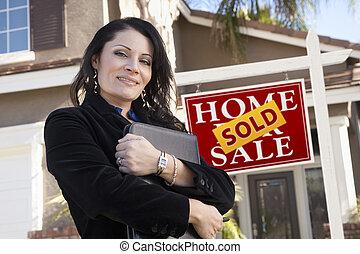 mujer hispana, delante de, signo bienes raíces, y, nuevo hogar