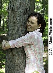 mujer joven, abrazar, un, árbol