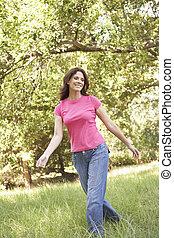 mujer joven, ambulante, por, césped largo, en el estacionamiento