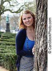 mujer joven, atrás, árbol